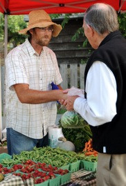 Brock McLeod serves a local customer at his vegetable stand